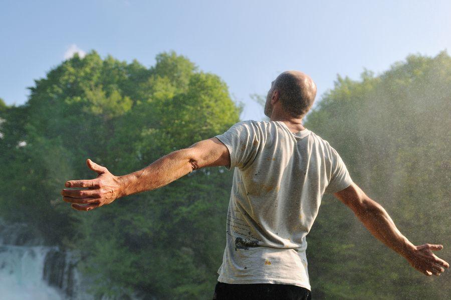 muž po sportu stojí s rozpřaženýma rukama a čerpá energii