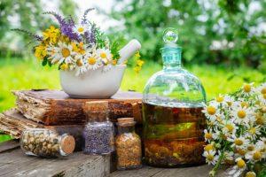miska s květinami, láhev a skleničky s přírodními léky